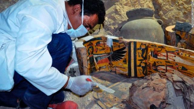 Un membro del gruppo di archeologi egiziani lavora su una bara di legno Martedì.