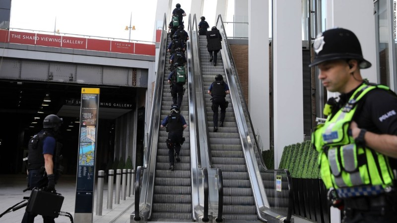 Counter Terrorism Officers Move Up An Escalator Under The Shard An Iconic Highrise Near The