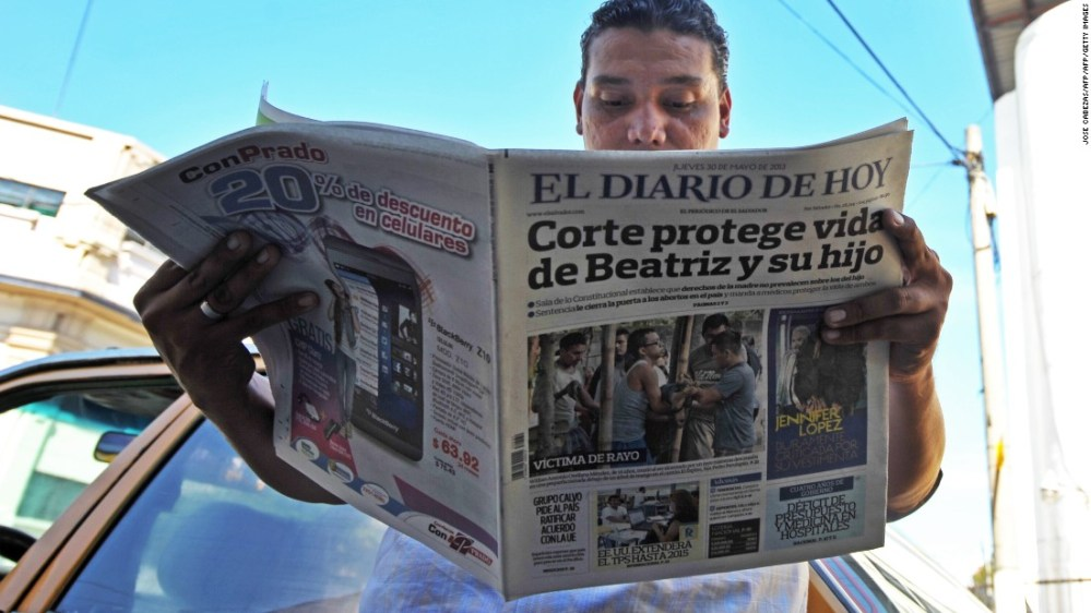 """A man reads a paper headlined: """"Court protects life of Beatriz and child."""" Beatriz, a chronically ill Salvadoran woman was denied an abortion in 2013, despite the fact her fetus was unviable."""