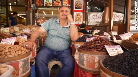 Hasan Dervisoglyu sits outside his spice and nuts stop near the Ankara castle.
