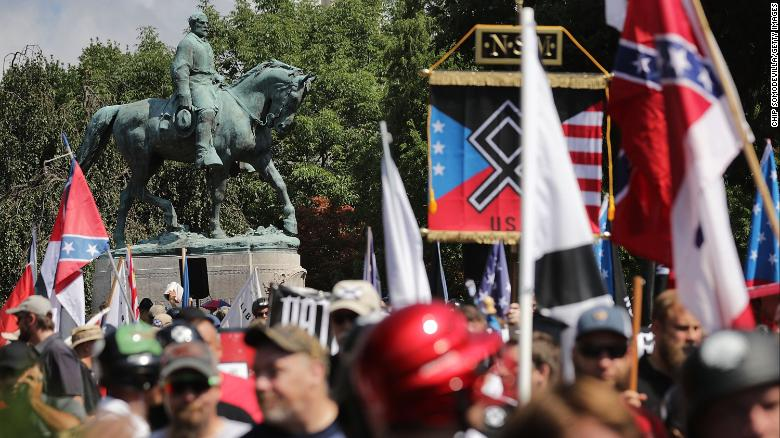 """A statue of Confederate General Robert E. Lee stands behind a crowd of white nationalists, neo-Nazis and members of the """"alt-right"""" movement during the """"Unite the Right"""" rally on August 12, 2017 in Charlottesville, Virginia. After clashes with counterprotesters and police, the rally was declared an unlawful gathering and protesters were forced out of Lee Park, where the statue is slated to be removed."""