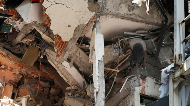A woman's crushed body hangs in a collapsed building in Mexico City on September 19.