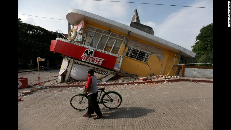 A man walks his bike past a partially collapsed building in Jojutla on September 20.