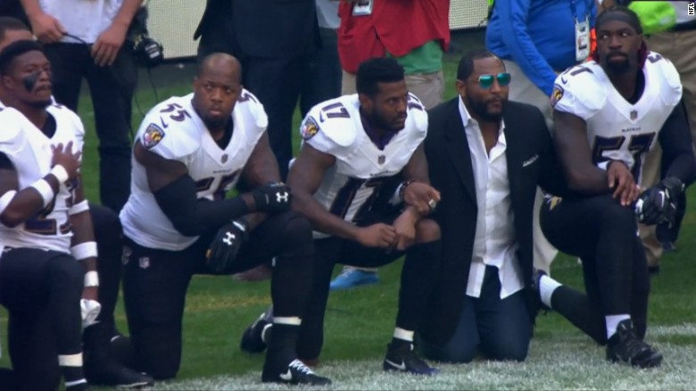 Retired Ravens linebacker Ray Lewis, in suit, joined his former team during Sunday's protest.