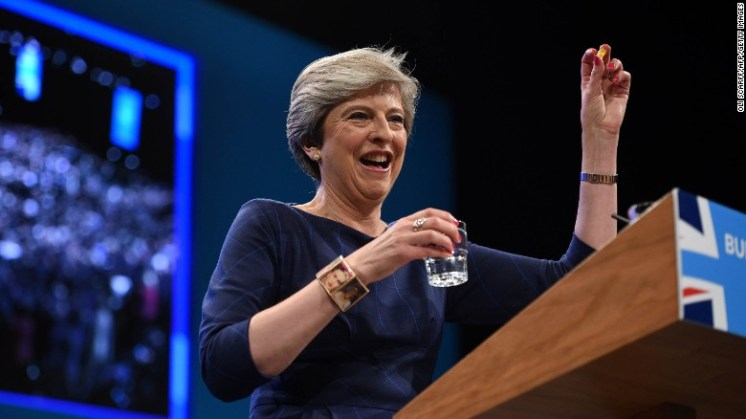 Britain's Prime Minister Theresa May holds up a throat lozenge given to her by Britain's Chancellor  Philip Hammond .