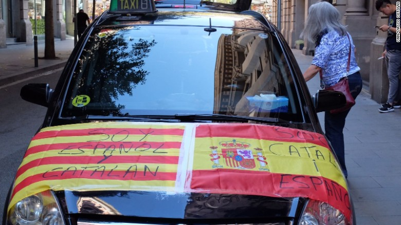 """A car is adorned with Spanish and Catalan flags reading """"I am Spanish and Catalan"""" and """"I am Catalan and Spanish."""""""