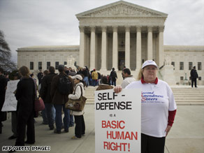 A gun ownership supporter holds a placard in March outside the Supreme Court in Washington.