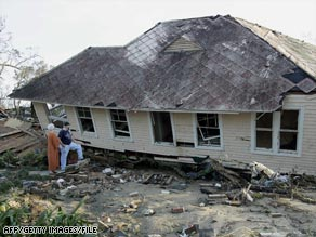 People check out the second story of a home sitting on the ground in Biloxi, Mississippi, after Katrina in 2005.
