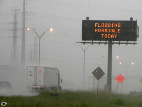A highway sign warns motorists as rains from tropical storm Edouard move across the state along Interstate 10 in Houston.