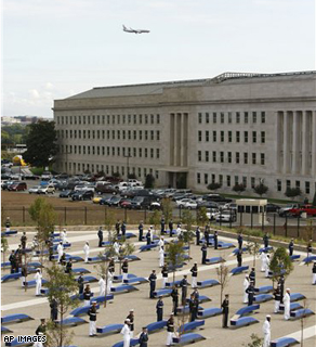 An airplane flies overhead toward Washington's Ronald Reagan National Airport as members of a Military honor guard stand at attention for the unveiling of the benches at the Pentagon Memorial, Thursday, Sept. 11,2008