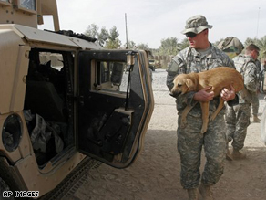 A U.S. soldier of 101st Airborne Division carries a dog before putting it in an army vehicle leaving Inshon patrol base in Youssifiyah, Iraq, as U.S troops handed over the camp to the Iraqi army Monday