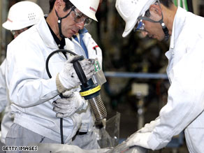 Employees of Nissan Motor Company work on the assembly line in Japan.