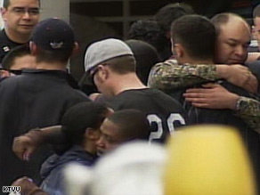 Officers console each other outside the Oakland hospital where their colleagues are in critical condition.