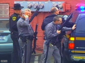 Armed law enforcement officers gather at the scene of Friday's shootings in Binghamton, New York.