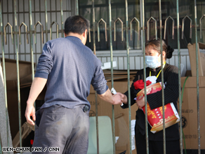 An employee at a Beijing hotel that is under quarantine receives supplies from her husband Sunday.