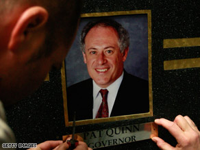 A worker replaces ousted Illinois Gov. Rod Blagojevich's picture with that of Pat Quinn.