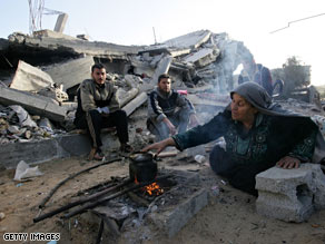 A Palestinian woman makes tea on a wood fire as she sits with her sons amid the rubble of houses in Gaza.