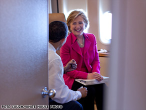 President Obama and Secretary of State Hillary Clinton share a conversation on board Air Force One.