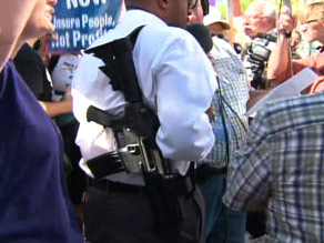 A man is shown legally carrying a rifle at a protest against President Obama in Phoenix, Arizona in August.