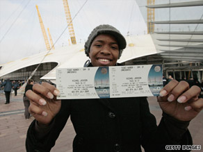 A fan shows off the first ticket bought at the O2 Centre in London for one of Michael Jackson's concerts.