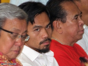 Philippine boxing champ Manny Pacquiao sits with Secretary of Environment and Natural Resources Lito Atienza (L) and former governor Chavit Singson (R) in Manila.