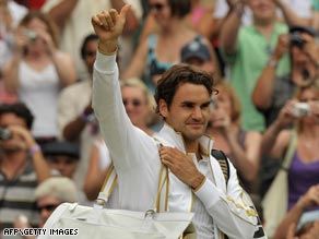 Federer gives a thumbs-up after reaching the last eight at Wimbledon where he is chasing a grand slam record win.