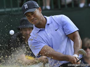 Tiger Woods chips out of a bunker during his opening round at the Hazeltine National Golf Club in Chaska.