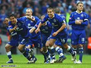 Everton's players charge forward with delight after Jagielka's winning penalty.