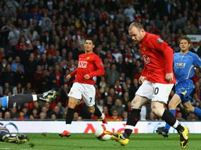 Wayne Rooney puts Manchester United ahead as they moved three points clear of Liverpool.
