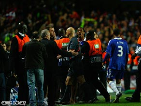 Didier Drogba confronts referee Tom Henning after Chelsea's dramatic Champions League exit.