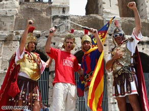 United and Barcelona fans, dressed as centurions, pose together outside Rome's Colosseum.