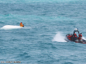Nick Schuyler clings to an overturned boat in this Coast Guard photo.