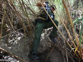 A Border Patrol agent moves through dense cane on the banks of the Rio Grande near Laredo, Texas, last year.