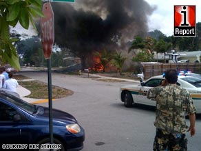 Bystanders watch the flames after the plane crash Friday in Fort Lauderdale, Florida.