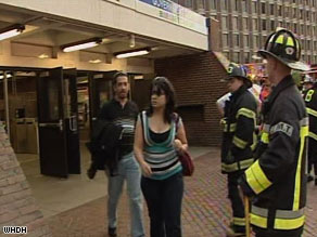 Passengers walk past firefighters at a Green Line station in Boston after trolley collision Friday evening.
