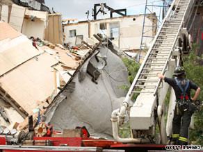 A firefighter surveys the scene of a collapsed building in Brooklyn on Sunday. Four people received minor injuries.