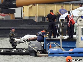 Divers unload a body from their raft onto a police boat Sunday. Nine people are believed dead in the crash.