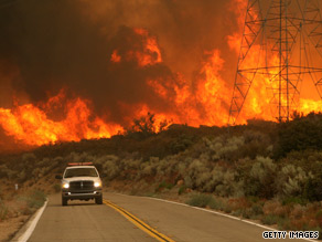 A firefighter speeds away from a dangerous wall of flames in Acton, California, on Sunday.