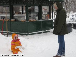 A girl plays in the snow Monday in New York, where schools closed for the first snow day in five years.