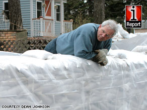 A Fargo resident surveys sandbags Tuesday outside his home, located about 15 feet from the Red River.