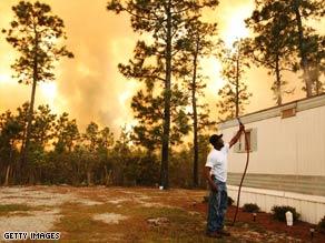 Scott Vereen sprays water on his family's home Thursday near Conway, South Carolina.