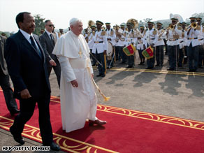Cameroonian President Paul Biya, left, walks with Pope Benedict XVI at the airport in Yaounde, Tuesday.