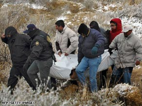 Mexican police carry a body after a clash with gangs that left 21 dead in the state of Chihuahua on February 10.