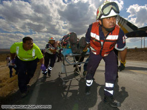Emergency workers wheel a crash victim on a gurney after Monday's bus crash in Mexico.