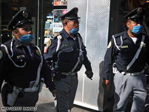 Police officers take precautions against the swine flu outbreak as they patrol streets Wednesday in Mexico City.