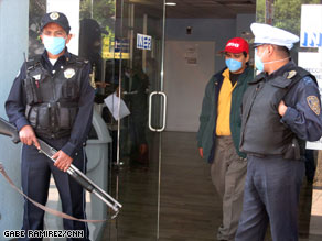 Armed guards stand outside the Mexico City Respiratory Hospital to control the flow of people.