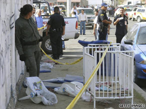 A crib and baby seats lie outside a day care center Friday in Hermosillo, Mexico, as police cordon off the area.