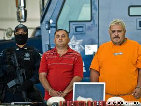Alleged drug traffickers Miguel Angel Beraza Villa, middle, and Rafael Hernandez face the press Monday.