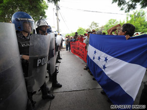 Riot police stand in front of marchers supporting ousted Honduran President Manuel Zelaya on Tuesday.