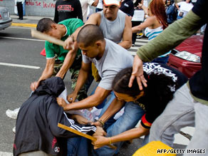 A group of pro-Hugo Chavez rioters beats Venezuelan journalists in downtown Caracas on August 13.
